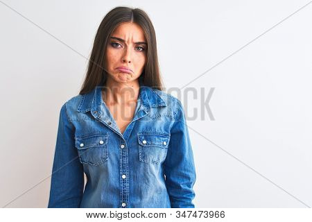 Young beautiful woman wearing casual denim shirt standing over isolated white background depressed and worry for distress, crying angry and afraid. Sad expression. stock photo