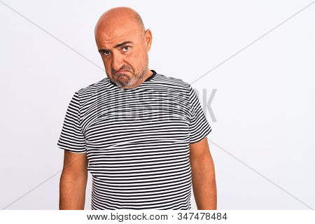 Middle age handsome man wearing striped navy t-shirt over isolated white background depressed and worry for distress, crying angry and afraid. Sad expression. stock photo