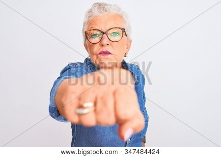 Senior grey-haired woman wearing denim shirt and glasses over isolated white background Punching fist to fight, aggressive and angry attack, threat and violence stock photo