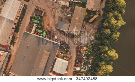 Aerial view of warehouse storages or industrial factory or logistics center from above. Aerial view of industrial buildings and equipment machines at sunset stock photo