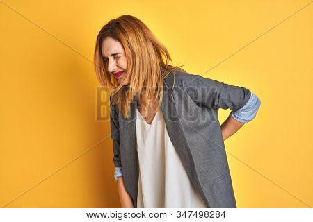 Redhead caucasian business woman over yellow isolated background Punching fist to fight, aggressive and angry attack, threat and violence stock photo