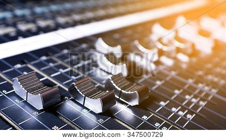 Microphones, Amplifying Equipment, Studio Audio Mixer Knobs And Faders, Background Audio Mixer. Workplace And Equipment Of The Sound Engineer. Acoustic Music Mixing, Selective Focus. Tinted photo. stock photo