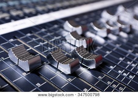 Microphones, Amplifying Equipment, Studio Audio Mixer Knobs And Faders, Background Audio Mixer. Workplace And Equipment Of The Sound Engineer. Sound, Acoustic Music Mixing, Selective Focus. stock photo