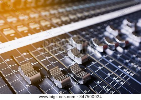 Microphones, Amplifying Equipment, Studio Audio Mixer Knobs And Faders, Background Audio Mixer. Workplace And Equipment Of The Sound Engineer. Acoustic Music Mixing, Selective Focus. Tinted photo stock photo