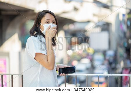 Woman wearing face mask protect filter against air pollution (PM2.5) or wear N95 mask. protect pollution, anti smog and viruses, Air pollution caused health problem. environmental pollution concept. stock photo