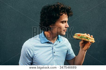 Side view image of young handsome man eating a healthy burger. Hungry man in a fast food restaurant eating a hamburger outdoors. Man with curly hair having street food and eat a burger. stock photo