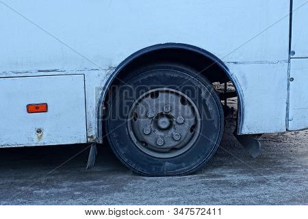 part of an old white bus with one black wheel on gray asphalt street stock photo