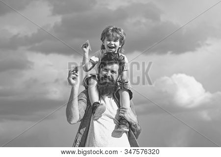 Generation. Father giving son ride on back in park. Father and son building together a paper airplane. Portrait of happy father giving son piggyback ride on his shoulders and looking up stock photo