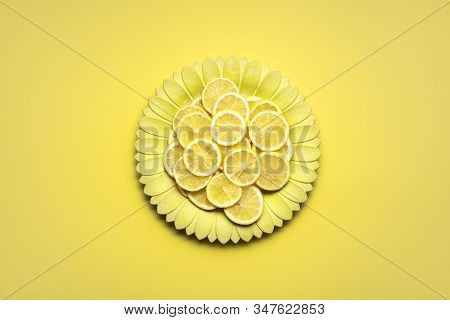 Slices of lemons on a yellow flower-shaped dish on yellow background. Sliced lemons on a plate. A minimalist image in yellow shades. Summer fruits. stock photo