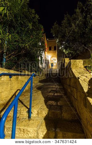 The picturesque alleys of Old Jaffa. Old Jaffa - one of the most ancient cities of the world. Night. Evening lights illuminate the stone pavement.  stock photo