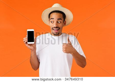 Amused young african-american male student seeing great cheap tickets, book hotel with application, show thumb-up recommend app, looking smartphone screen with smile, orange background stock photo