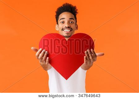 Guy giving his love you. Handsome lovely african-american man stretching hands and presenting red heart, smiling, showing true love and sympahy, express affection, standing orange background stock photo