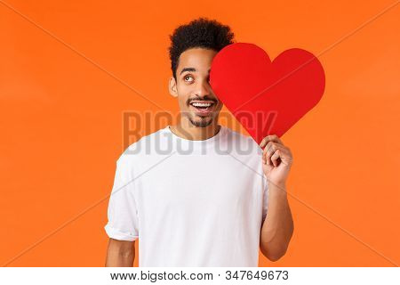Dreamy handsome african-american guy found true love, giving valentines card to lover, looking upbeat up thoughtful, imaging perfect date, express own love and affection, standing orange background stock photo
