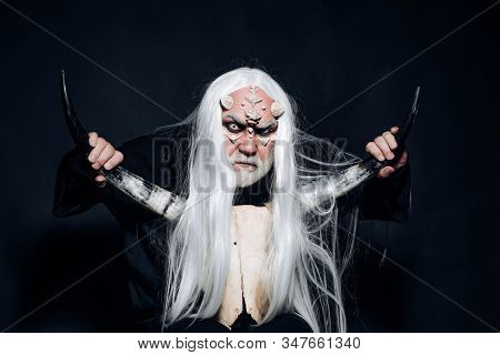 Demon with bloody horns on head. Demon head isolated on black. Man with a bull head. Alien with dragon skin and grey beard. Ancient alchemy. Viking with a horned head. Vampire man with white eyes stock photo