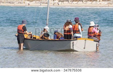 A team of teenagers adjusts a sailboat for the regatta stock photo