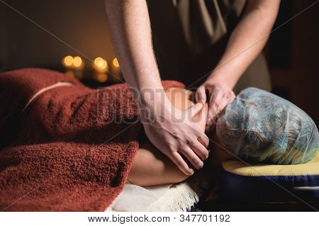 Professional massage of the shoulder and trapezius muscle indoors with cozy dark lighting. Premium massage. Male physiotherapist massage therapist doing upper back massage to a female client stock photo