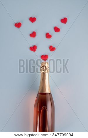 Valentines Day, anniversary or wedding celebration concept. Flat lay. Top view. Copy space. Hearts spray from a bottle of champagne. On pastel blue background. stock photo