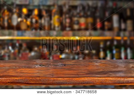 Wooden board on a background of bottles with alcohol. Old bar counter as layout for design. Workpiece for design. Empty place to advertise products. Blurred interior of the bar in the background. stock photo
