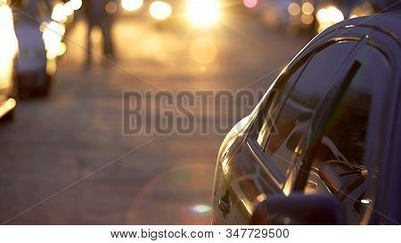 Automobile slowly driving on parking lot during magic sunset, auto park stock photo