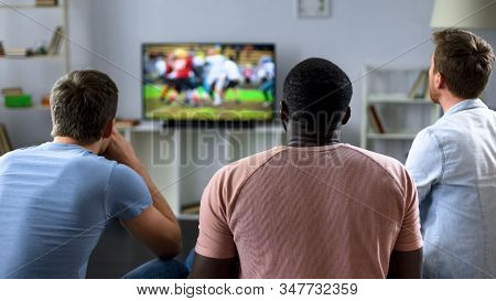 Guys actively cheering american football team, love for sport, leisure at home stock photo