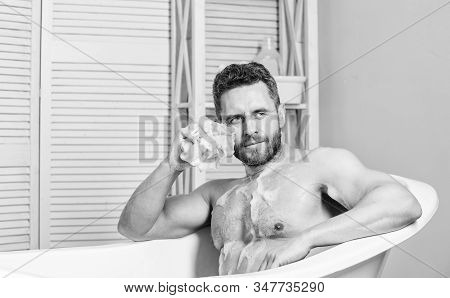 Transform your bathroom into own private spa. Macho with sponge take bath at home. Taking bath with soap suds. Pampering and beauty routine. Handsome muscular man relaxing bathtub. Warm bath concept stock photo