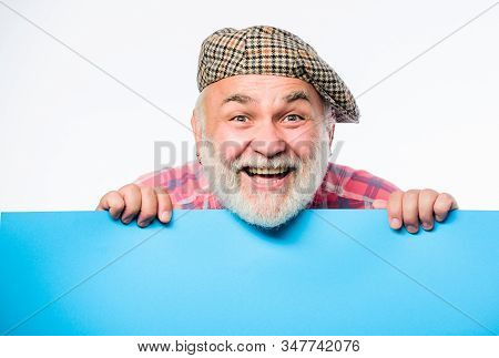 Senior bearded man peek out of banner place announcement. Advertisement shop. Pensioner grandfather in vintage hat hold poster information copy space. Event announcement. Announcement concept stock photo
