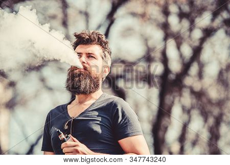 Stress relief concept. Bearded man smoking vape. Smoking electronic cigarette. Man long beard relaxed with smoking habit. Man with beard and mustache breathe out smoke. White clouds of flavored smoke stock photo
