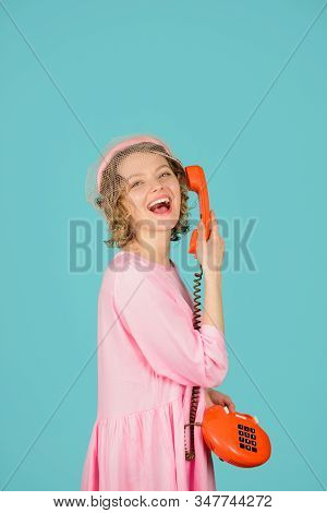 Communication. Girl talking on landline phone. Smiling girl talking on retro phone. Happy woman in pink dress with telephone handset. Smiling woman with handset. Pretty woman talking at retro handset. stock photo