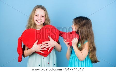 Sincere kids share tenderness and love. Girls hug red plush heart toy symbol love. Sisterhood concept. Valentines day. Friendly relations siblings. Family love. Happy feeling love. Loving sister stock photo