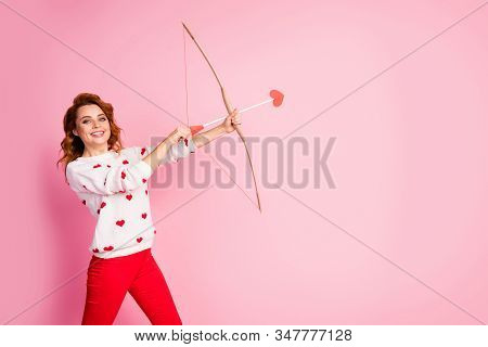 Portrait of her she nice attractive lovely pretty cute confident amorous cheerful cheery glad wavy-haired girl angel shooting arrow match making soulmate isolated on pink pastel color background stock photo