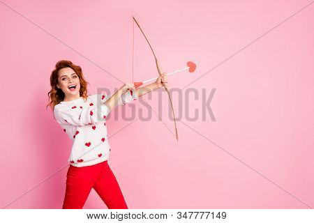 Portrait of her she nice attractive lovely pretty amorous cheerful cheery glad positive wavy-haired girl angel shooting arrow match isolated on pink pastel color background stock photo