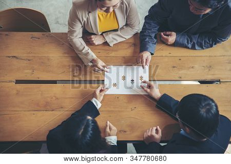 Strategy and Solution Business Concept.Group of Business people holding piece of jigsaw puzzle to solution problem on wooden desk,Collaborate between Professional Businessman and Partnership stock photo