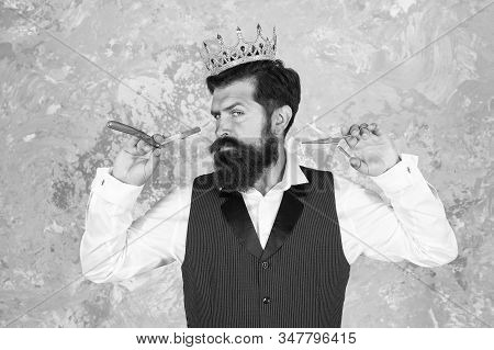 Noble worker. Crown award. Barber shop concept. Bearded hipster shaving. Vintage barber. Barber tools. Barber hold hairdresser equipment blade and scissors. Taking care facial hair. King of style. stock photo