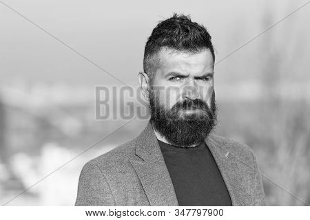 Hipster serious handsome attractive guy with long beard. Barber hairdresser salon. Guy stylish long beard. Fresh haircut. Man bearded hipster with mustache blue sky background. Beard grooming guide. stock photo