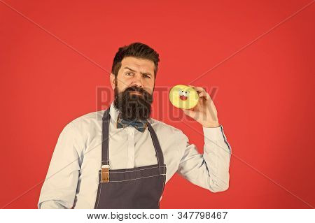 Get inspired by latest bakery and pastry trends. Pastry maker. Bearded man holding sweet baked pastry dessert on red background. Baking tasty pastry. stock photo