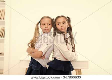 Schoolgirls standing back to back. Every day better. Little schoolgirls classmates friendly kids. Best friends relaxing. Schoolgirls tidy hairstyle relaxing having rest. Some kind of competition. stock photo