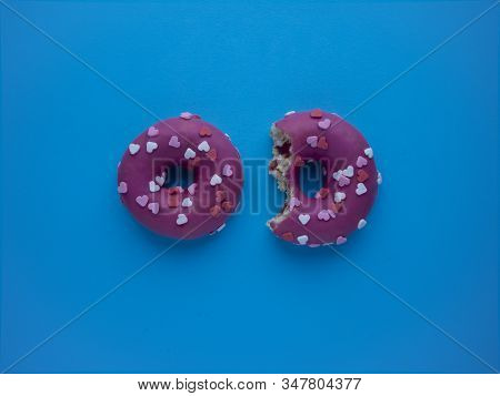 Two pink donuts decorated with glaze hearts  isolated on a blue background top view with copy space. One donut bitten. Sweet Valentine concept. Sweet-tooth, unhealthy diet, excessive consumption of flour and sweet. stock photo