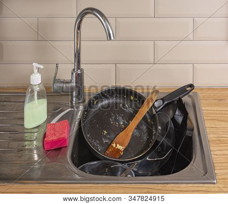 Doing house chores. Huge pile of dirty dishes to wash. A pile of dirty dishes in a dirty sink stock photo
