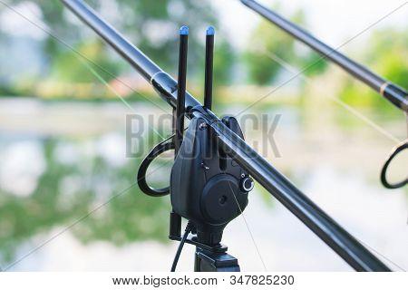 Professional carp fishing bite alarm, close-up from lakeside background. stock photo