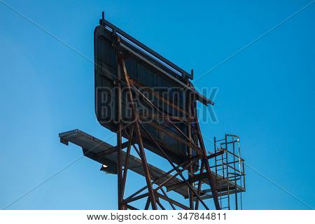 A low angle view of an old rusty roadside billboard sign. Seen from the back, steel frame construction, aging and weathered, against a clear blue sky stock photo