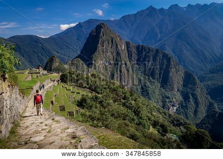 Man walking the Inca trail, the Huayna Picchu mountains behind. UNESCO World Heritage. Peru, South America stock photo