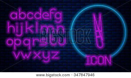 Glowing neon Eyebrow tweezers icon isolated on brick wall background. Cosmetic tweezers for ingrown hair. Neon light alphabet. Vector Illustration stock photo