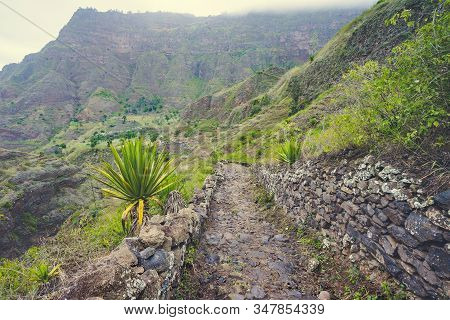 Santo Antao Cape Verde. Cobbled hike trail path leading down the valley. Rocky terrain of high mountain ranges and deep ravines in background stock photo