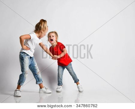 Elder girl sister is holding younger one painfully, abusing, stricting. Girl is crying, calling help Family conflict, violence, human relations concept on white with copy space stock photo