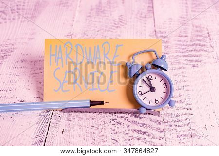 Handwriting text Hardware Service. Concept meaning act of supporting and maintaining computer hardware Mini blue alarm clock stand tilted above buffer wire in front of notepaper. stock photo