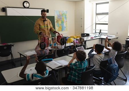 Front view of a schoolkids applauding while male Caucasian firefighter teaching about fire safety in classroom of elementary school stock photo
