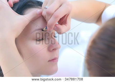 Cosmetologist painting shape of eyebrows for client woman before microblading procedure, side view, face closeup. Beautician preparing patient to beauty procedure. Young girl in beauty clinic. stock photo