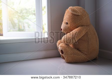 major depressive disorder mdd concept. Grief of children. Teddy bear sitting looking at the house window alone. Looks like someone who is sad, disappointed, depressed stock photo