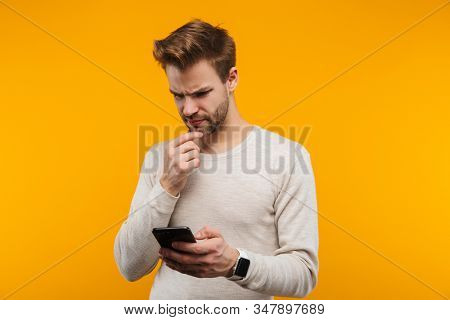Attractive confused young man wearing pullower standing isolated over yellow background, using mobile phone stock photo