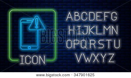 Glowing neon Mobile phone with exclamation mark icon isolated on brick wall background. Alert message smartphone notification. Neon light alphabet. Vector Illustration stock photo